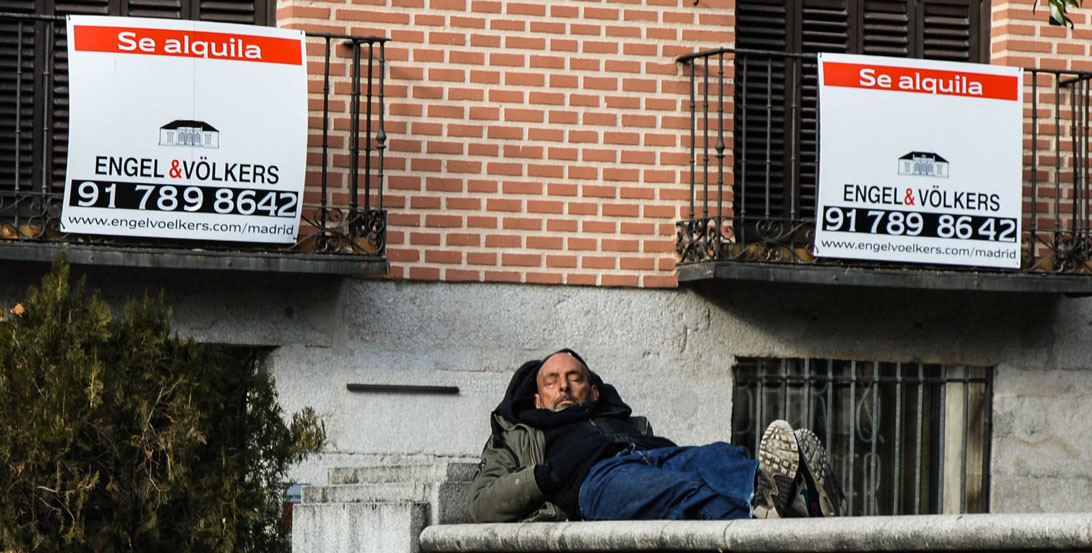 Homeless man next to a rent sign